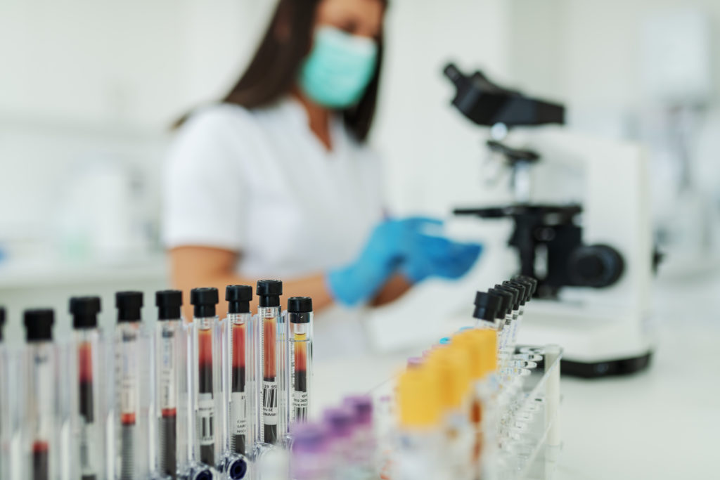 Pharmaceutical research scientist testing blood samples and creating clinical waste for removal